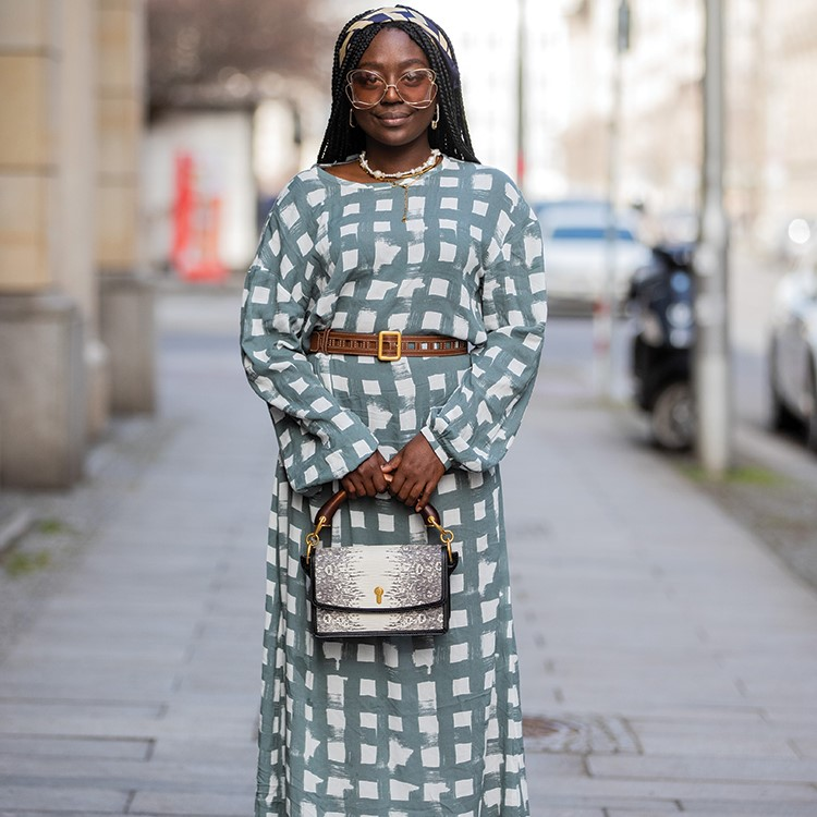 a person wearing a dress and holding a purse