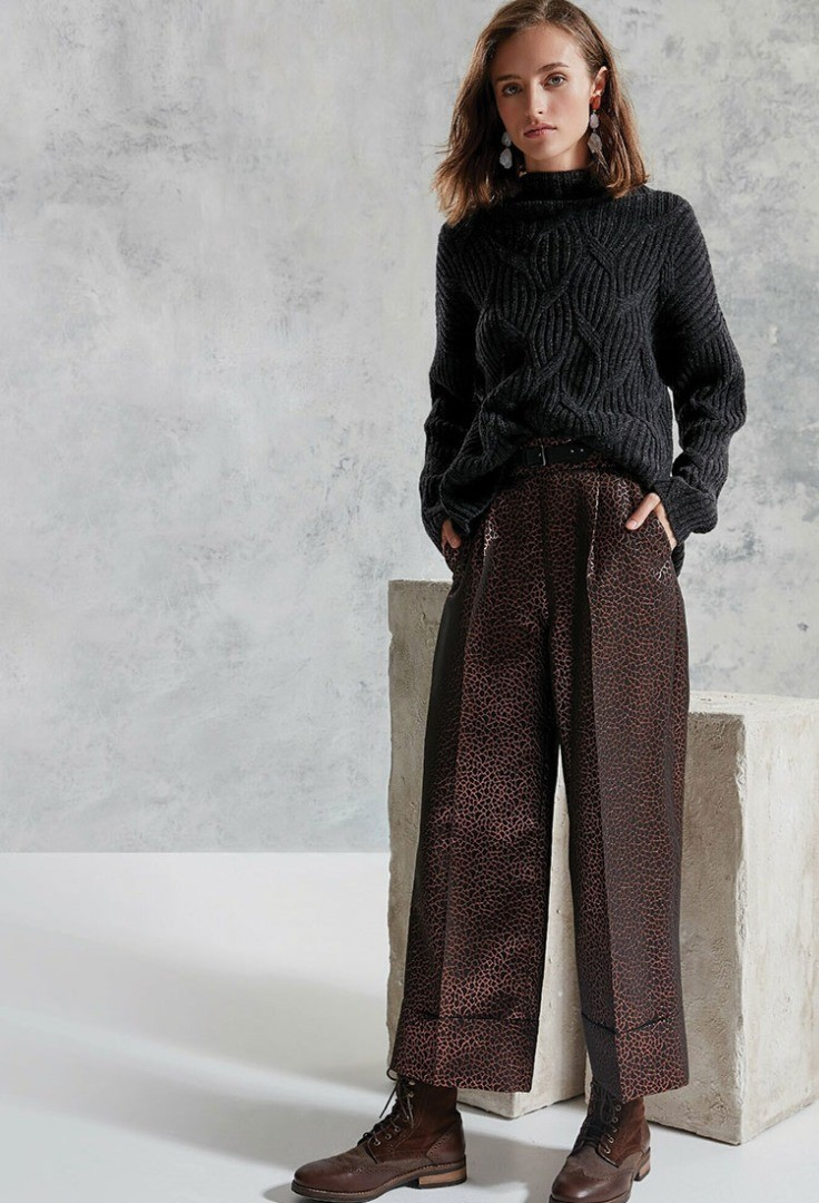 a woman wearing a black sweater and brown pants