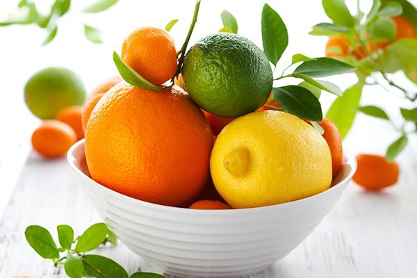 a bowl of oranges and limes