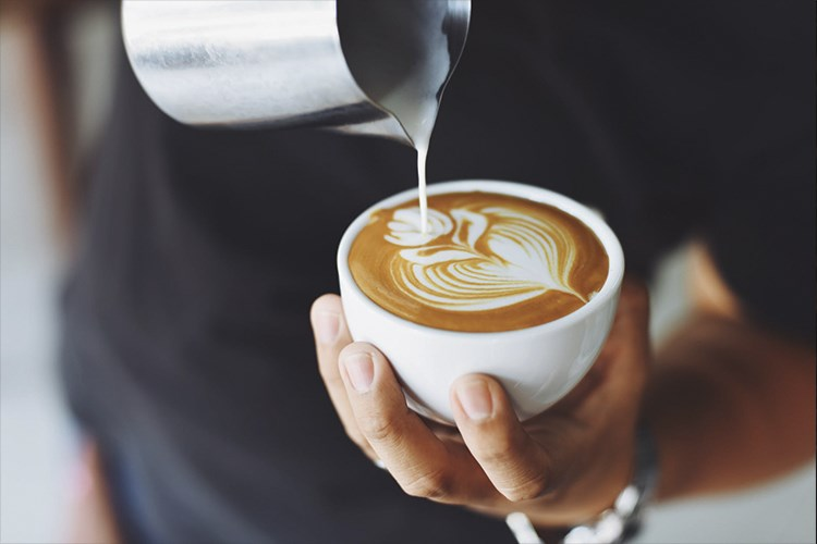 a person pouring a cup of coffee