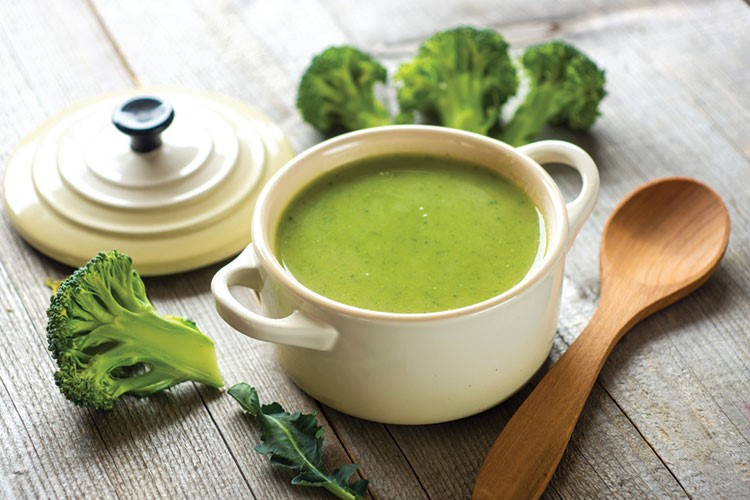 a cup of tea and broccoli on a wooden table