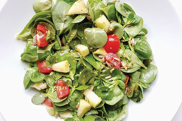 a salad with tomatoes and green leaves