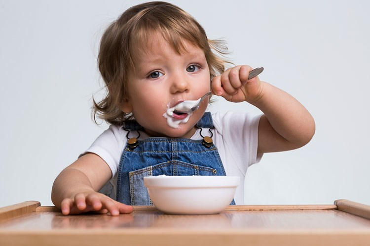 a baby eating from a bowl