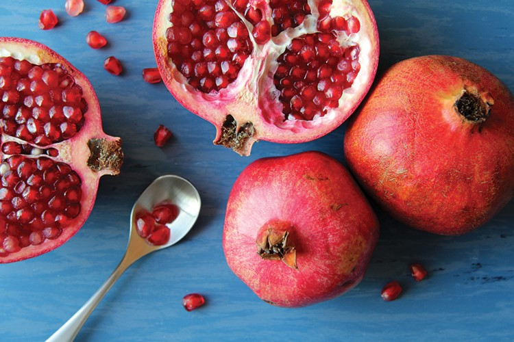 a group of pomegranates with a spoon