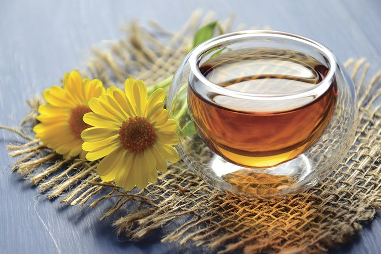 a glass of tea next to a flower and a cup of tea