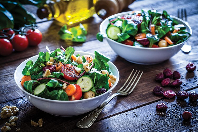 a bowl of salad and a bowl of salad on a table