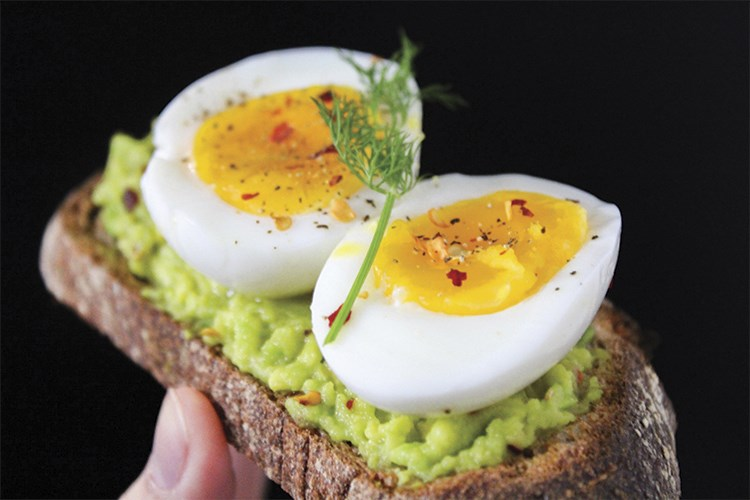 a hand holding a piece of bread with eggs and a green stem