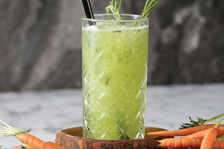 a glass of green liquid with a straw