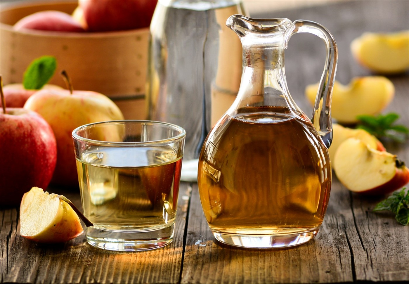 a glass of tea next to a pitcher of tea and apples