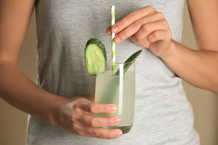 a person holding a glass with a drink and a lime in it