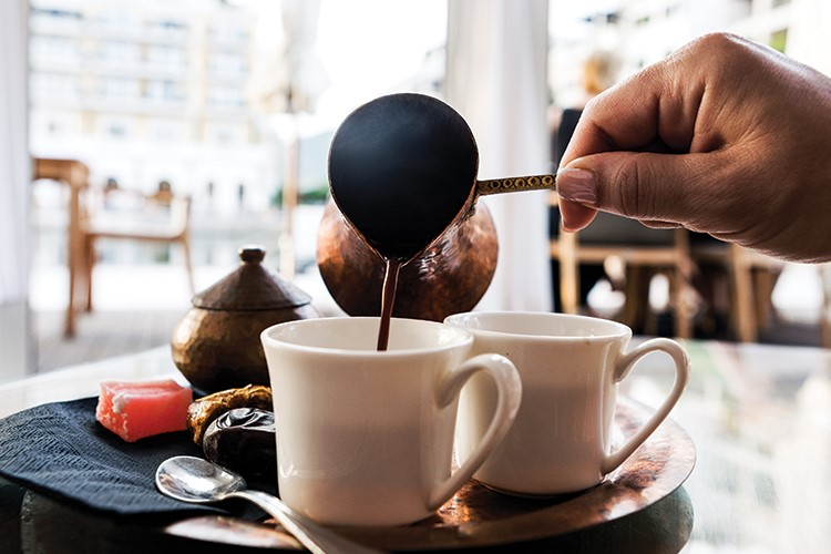 a person pouring a coffee into a cup