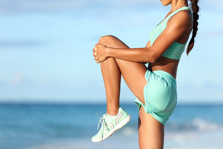 a woman in a green top and blue shorts stretching her legs