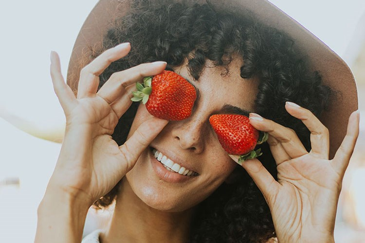 a person holding a strawberry