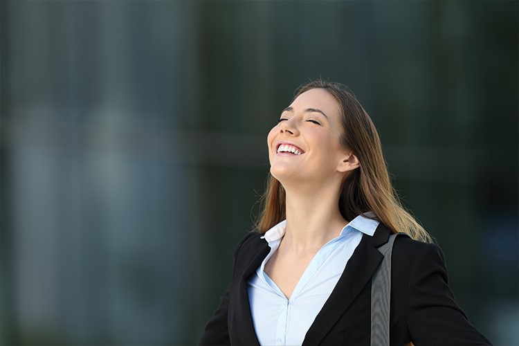 a woman smiling with her eyes closed