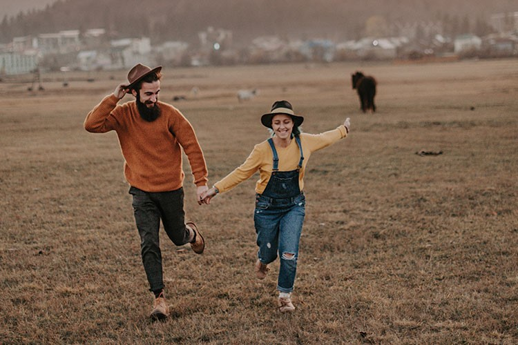 a man and woman running in a field