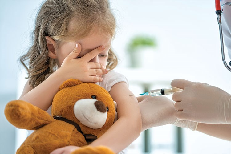 a young girl with a stethoscope and a teddy bear