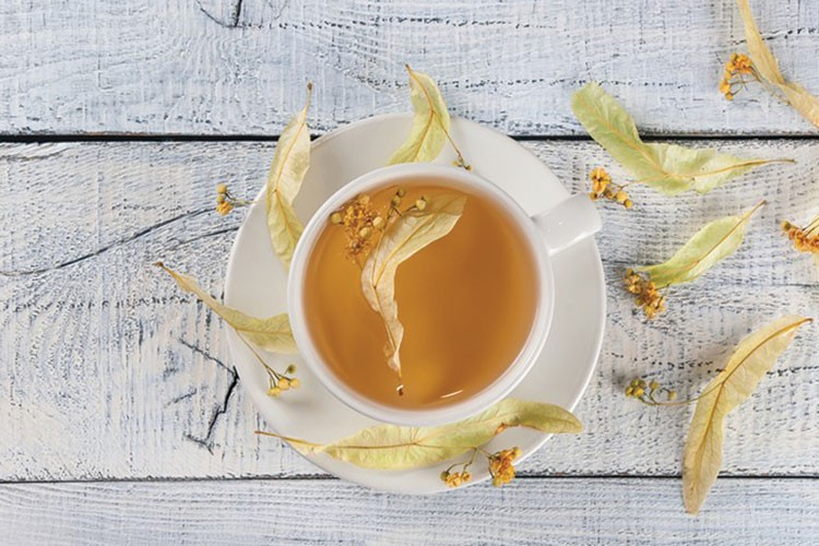 a cup of tea with leaves on the side