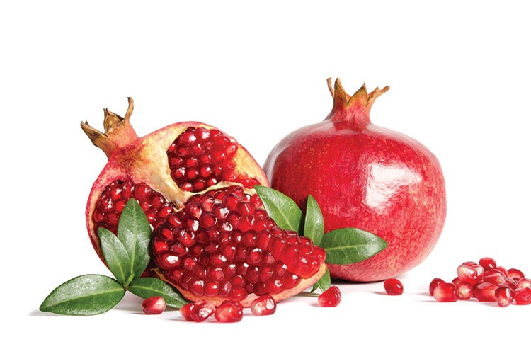 a couple of pomegranates with leaves and berries