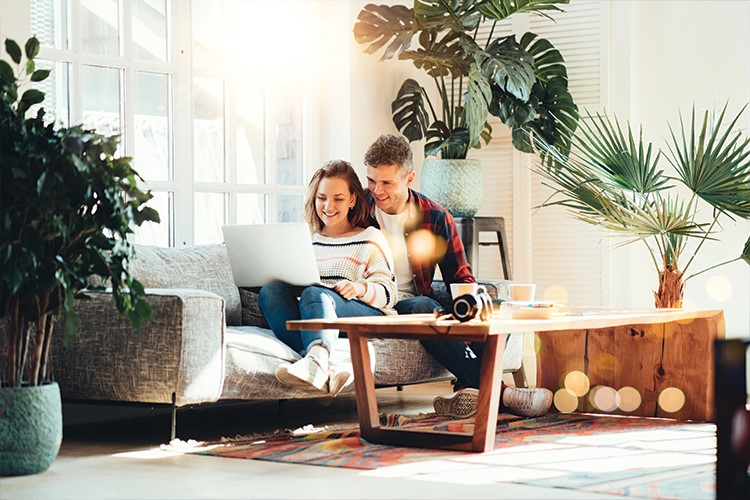 a man and a woman sitting on a couch with a laptop