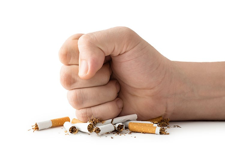 a hand holding a handful of cigarettes