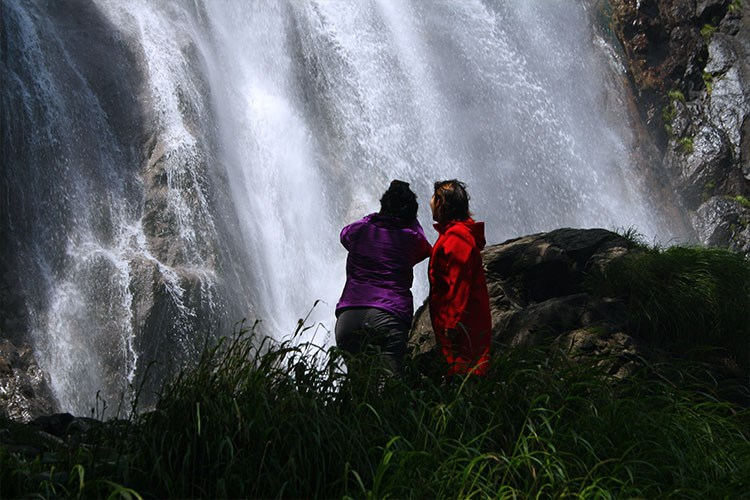 two people standing in front of a waterfall