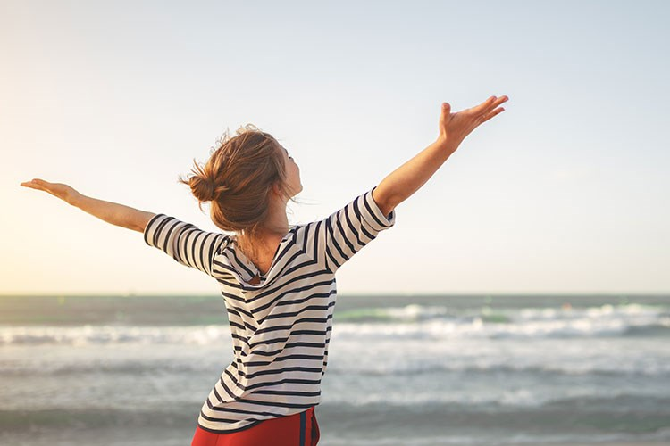 a person with the arms raised in front of the ocean