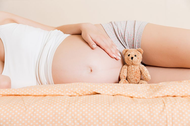a woman lays on a bed with a teddy bear