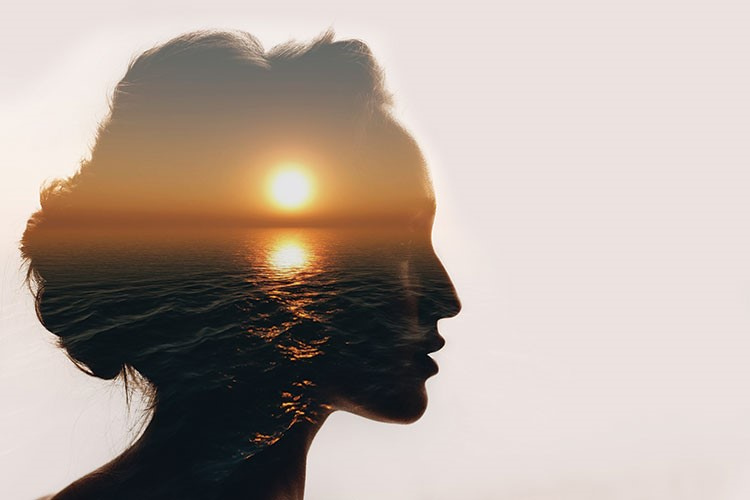 a woman's profile with the sun behind her