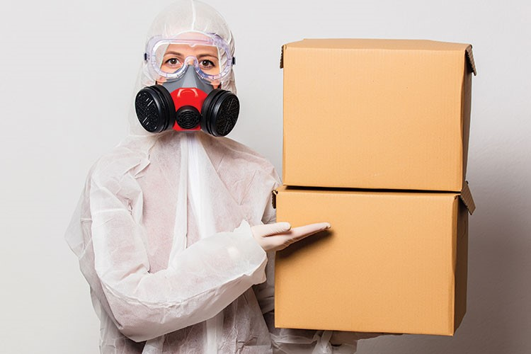 a person in a white suit holding a box and a mask