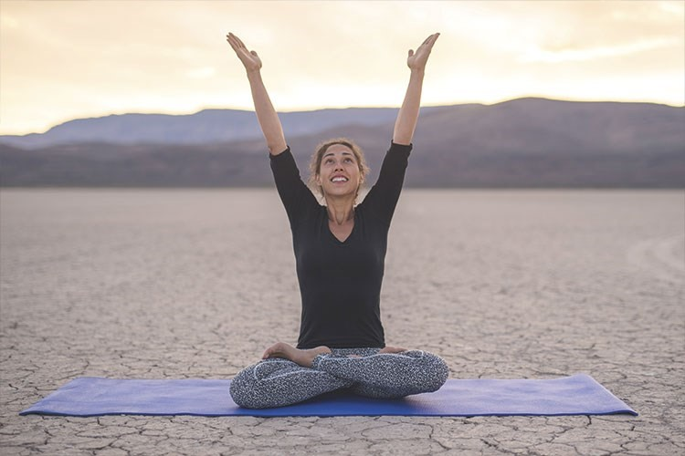 a person doing yoga on a beach