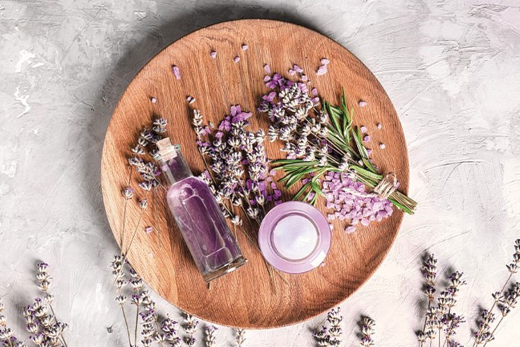 a wooden board with flowers and a candle on it