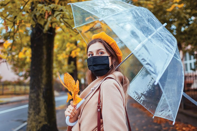 a person with a mask and umbrella
