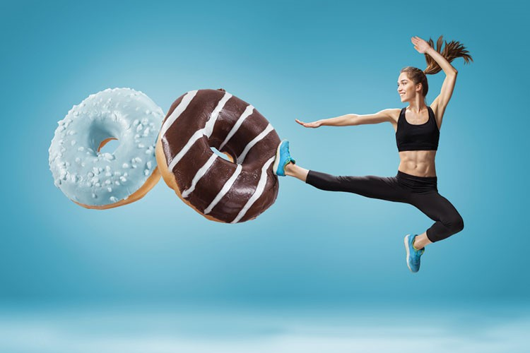 a woman jumping in the air with a donut in the air