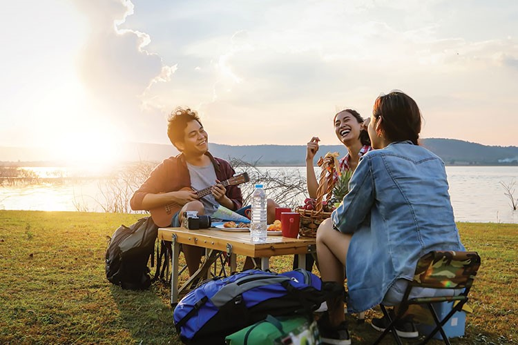 a group of people sitting at a picnic table on a grassy hill