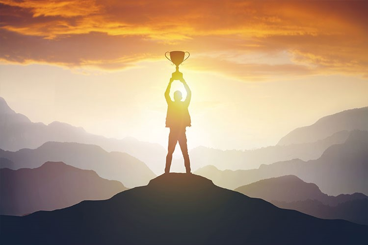 a person standing on a rock with a sun behind them