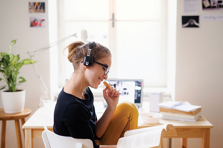 a woman wearing headphones and eating a hot dog