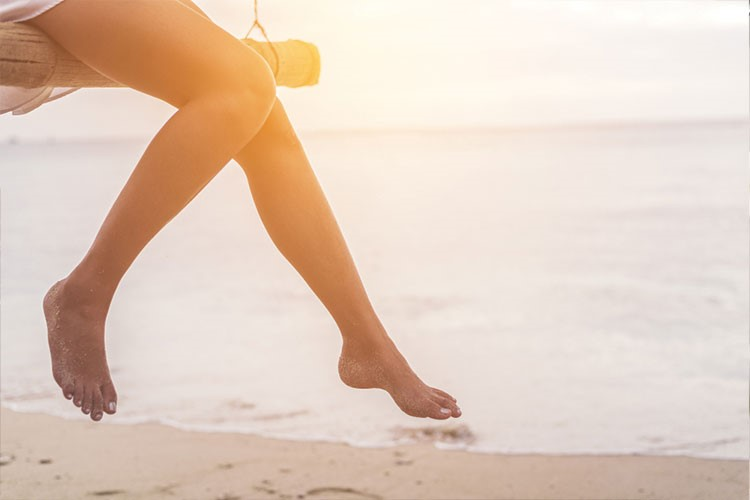 a person's legs and feet on a beach