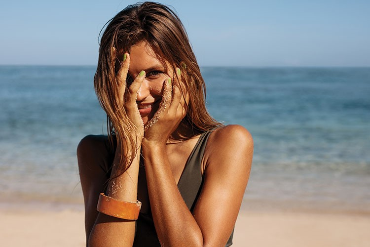 a woman with her hands on her face on a beach