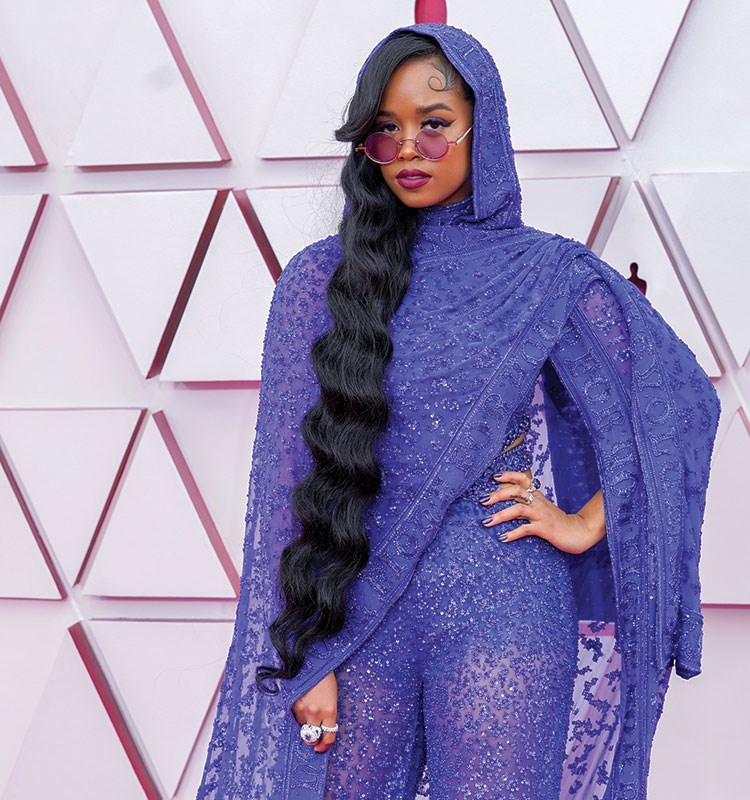 H.E.R. wearing a purple robe and glasses