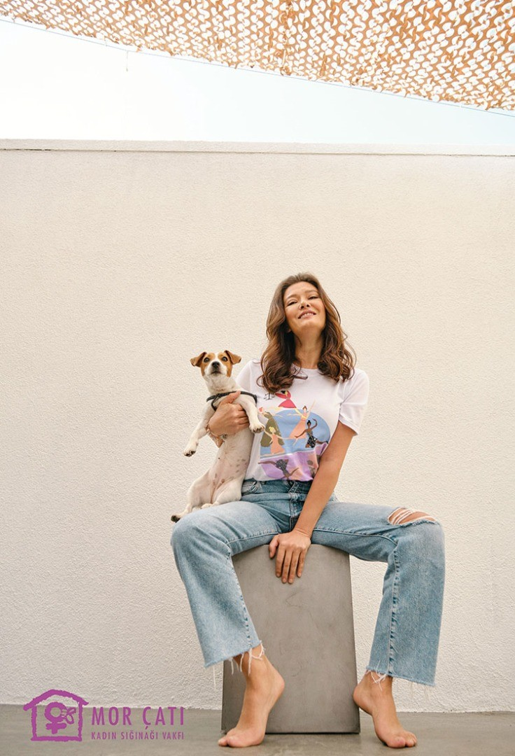 a woman sitting on a step holding a dog