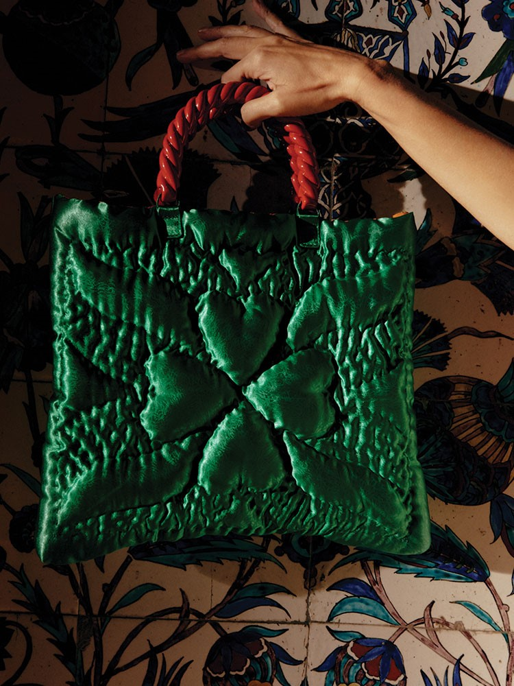 a hand holding a green and red bag with a red ribbon