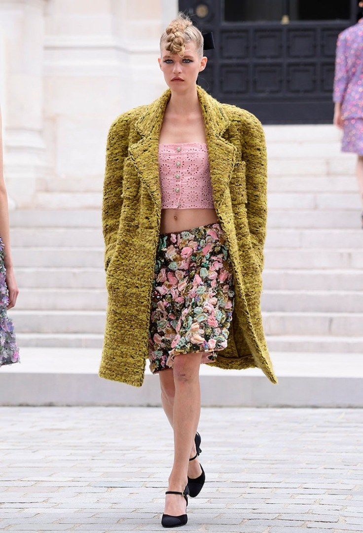 a person wearing a green and yellow dress and a pink jacket