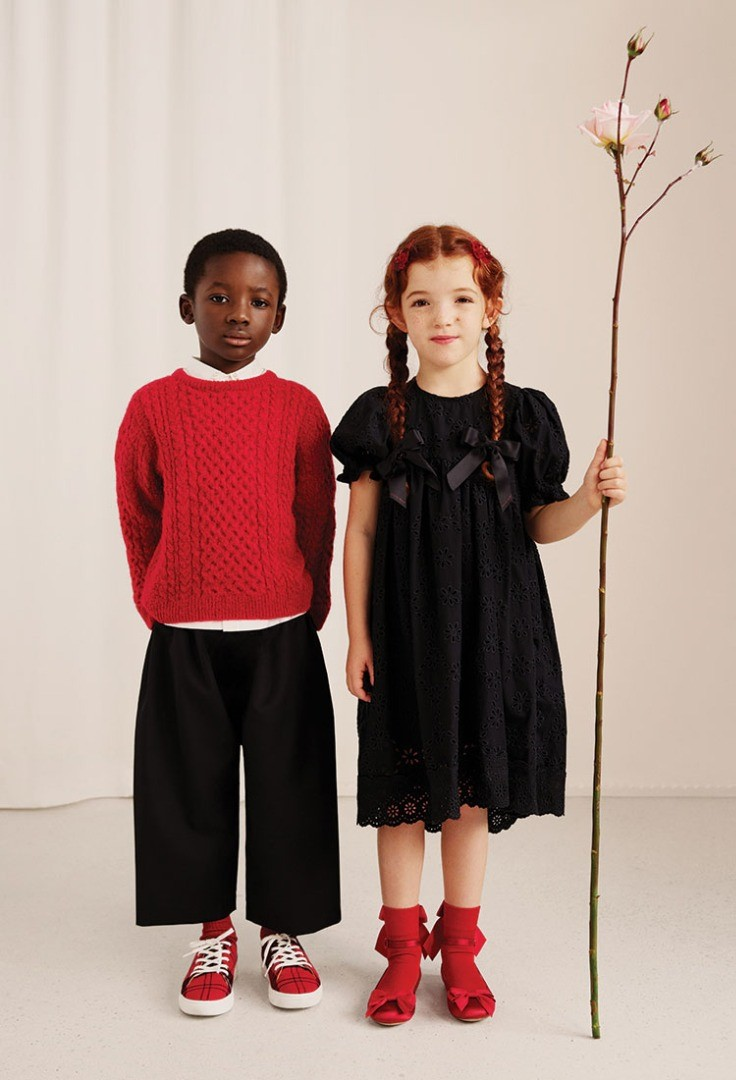 a boy and girl holding a flower
