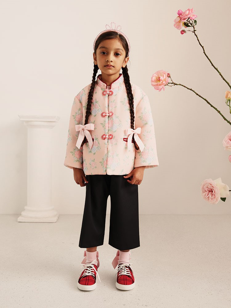 a girl wearing a white shirt and black pants with a white flower on her head