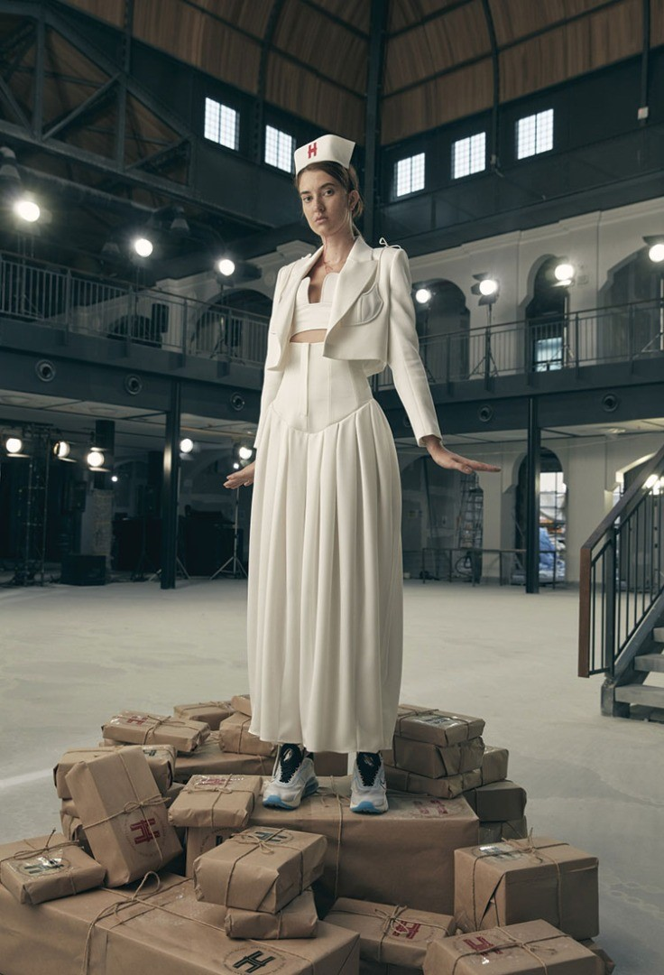 a person in a white dress standing on a pile of luggage