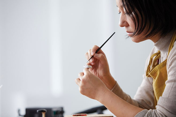a woman writing on a black marker
