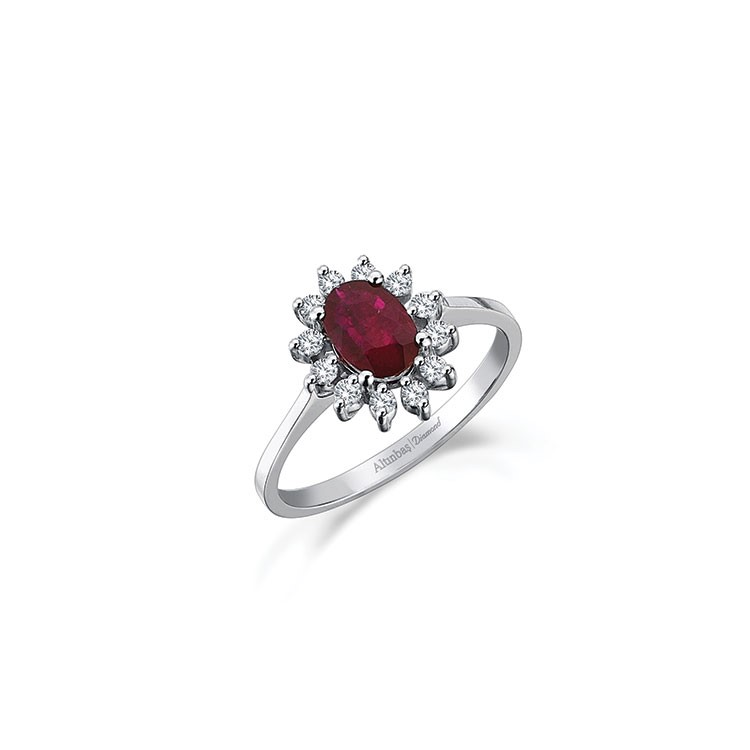 a diamond ring with a red gem