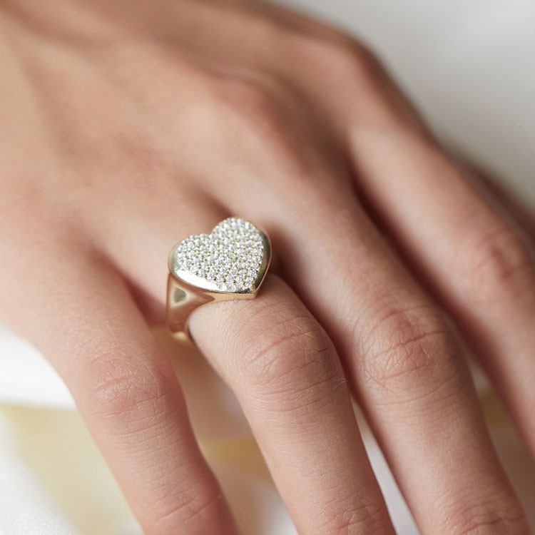 a person holding a small gold ring