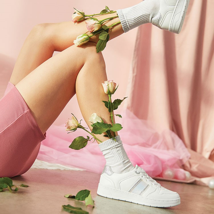 a woman's feet with white shoes and white shoes