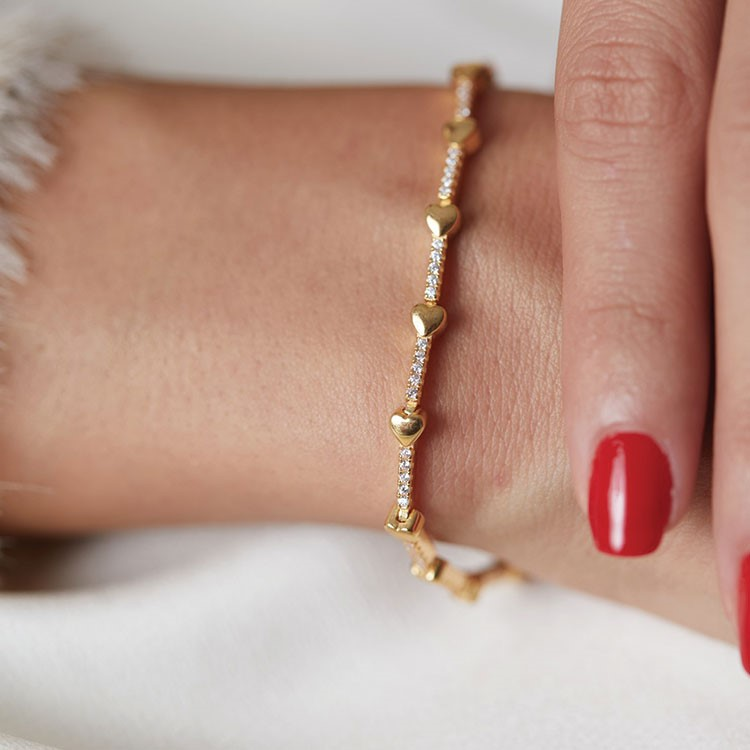 a woman's hand with a gold chain on her necklace